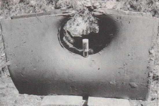 Wirkung eines Brenneke-Flintenlaufgeschosses aus 10 m Entfernung auf einen 15 cm dicken Tonblock (in der Höhlung steht eine ganze Patrone dieses Typs).